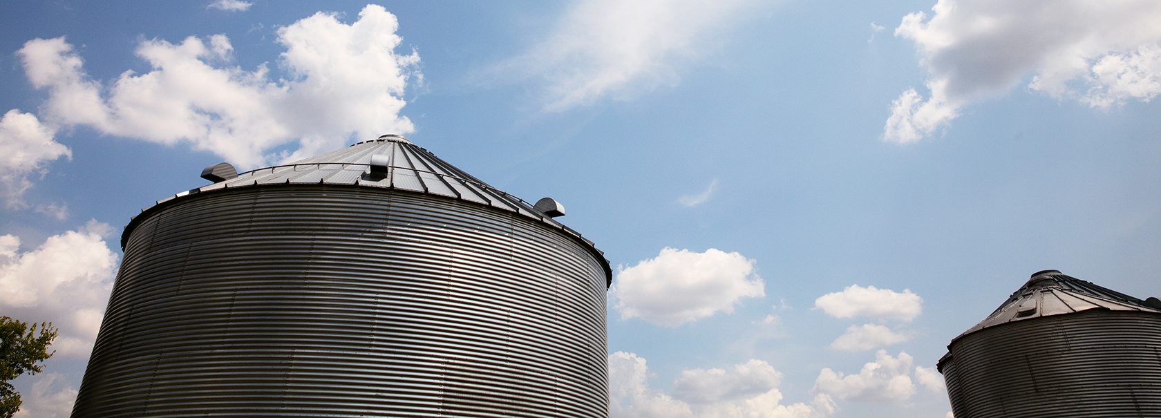 grain bins against blue skies